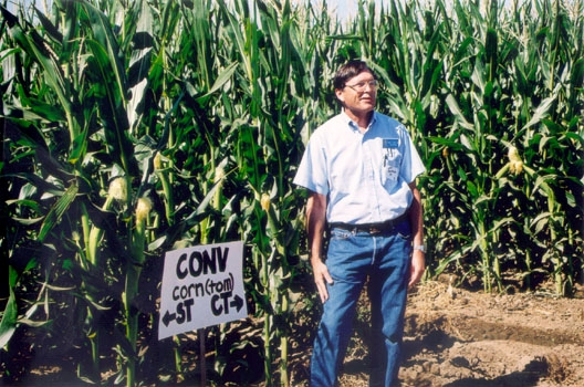 Kent Brittan stands at the edge of a field of corn that is taller than he is.