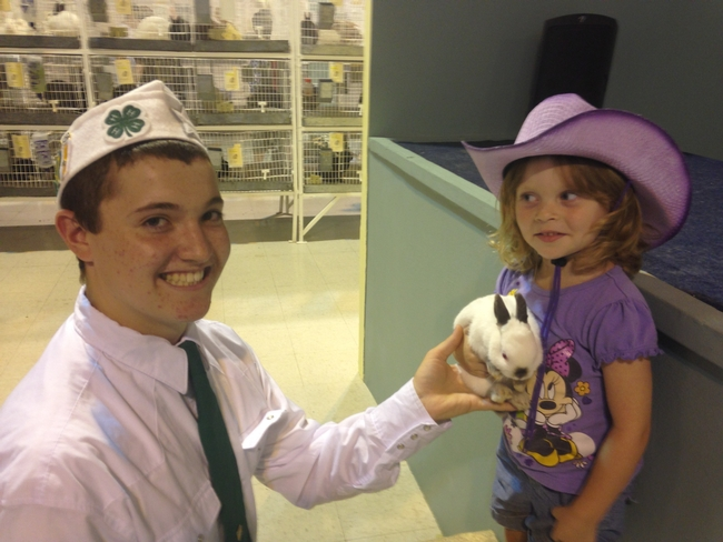 A boy in a 4-H uniform holds a small rabbit out to a small girl.
