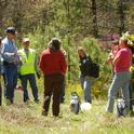 Glenn Nader, wearing blue cap, in the field with ranchers.