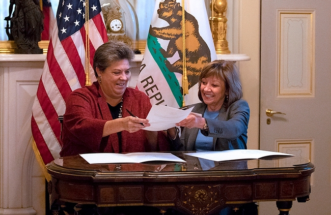 UC ANR vice president Glenda Humiston (left), and California Secretary of Agriculture Karen Ross sign a memorandum of understanding to initiate the new partnership to advance climate-smart agriculture.