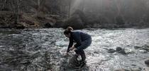 Tracy Schohr samples water in a stream in Butte County below the town of Paradise. Photo by Ryan Schohr for ANR news releases Blog