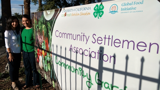 Claudia Diaz Carrasco and Emma Sandoval pose outside the Community Settlement Association banner in East Riverside