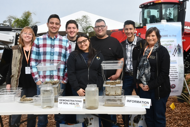 Mira Dick, USDA NRCS Merced (far left) and Sheryl Feit, USDA NRCS Davis (far right) conduct soil health demonstation at the joint CASI and NRCS display site at the 2019 World Ag Expo in Tulare, CA