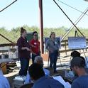 Emily Lovell (left), Shulamit Shroder (center), and Caddie Bergren (right) sharing with field educational event participants information about the CDFA Healthy Soils and State Water Efficiency Enhancement Programs