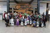 CS Pathway Team, volunteers, Googlers, and youth participants posing in front of a Google sign.