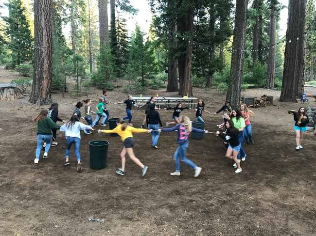 Youth outdoors running in a circle holding hands