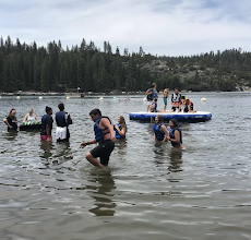 Lake with youth in water and on top of a floating inflatable dock.