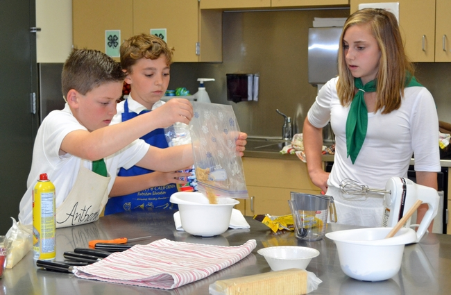 Elisabeth Watkins, winner of the 2019 4-H Youth in Action Award for Healthy Living, mentoring younger 4-H member on a cooking project.