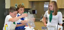 Elisabeth Watkins, winner of the 2019 4-H Youth in Action Award for Healthy Living, mentoring younger 4-H member on a cooking project. for Healthy Communities Blog Blog