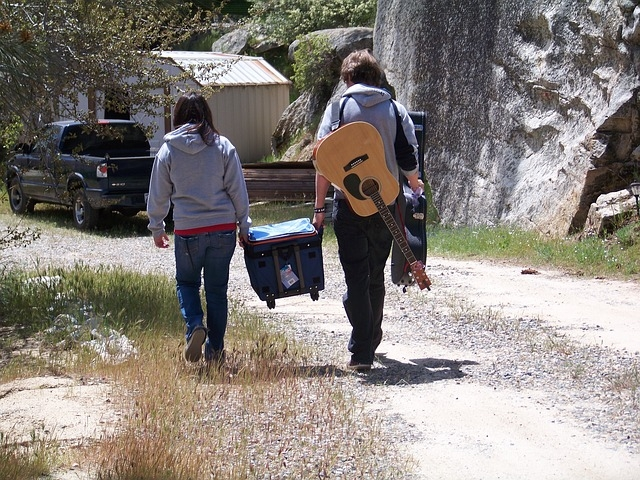 Couple walking in outdoor area with guitar and ice chest.
