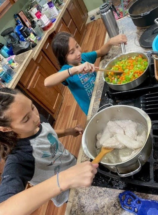 2 youth at stove stirring ingredients in 2 pots