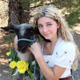 Blonde-haired girl poses next to lamb that is wearing a wreath of yellow roses around its neck.