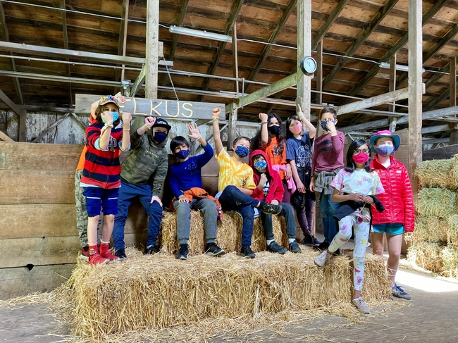 Ten students sit on straw bales raising their forearms to show off the bracelets they made from sheep wool.