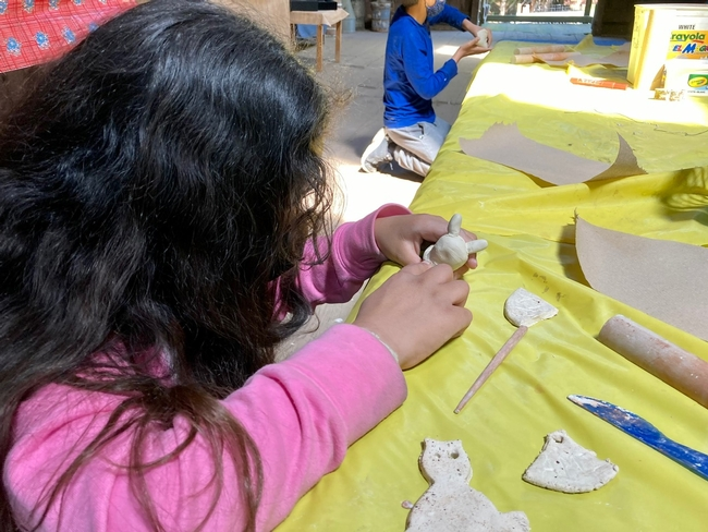 A girls with long dark, wavy hair and a pink jacket uses her fingers to form a bunny out of clay.