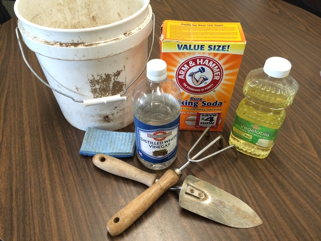 Baking soda, vinegar, vegetable oil, and a scrubber with garden tools.
