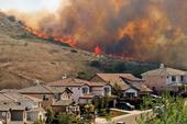 Flames and smoke fill the sky behind a Southern California subdivision.
