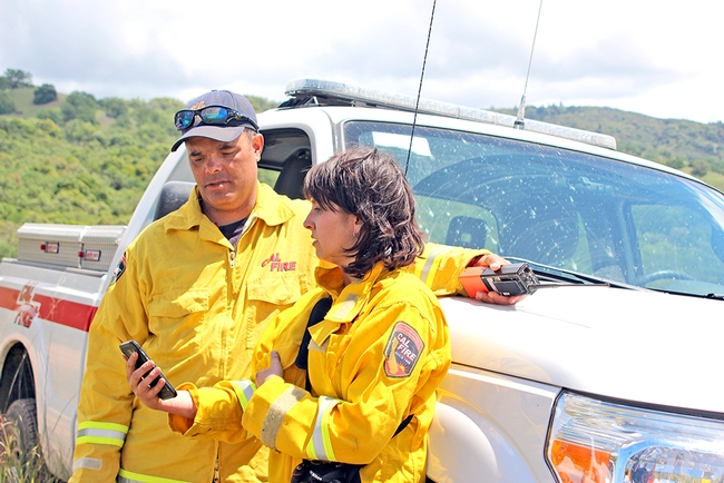 CalFire battalion chief Mike Maynard, left, discusses the controlled burn with researcher Lindsey Hendricks-Franco. (Photo: Evett Kilmartin)