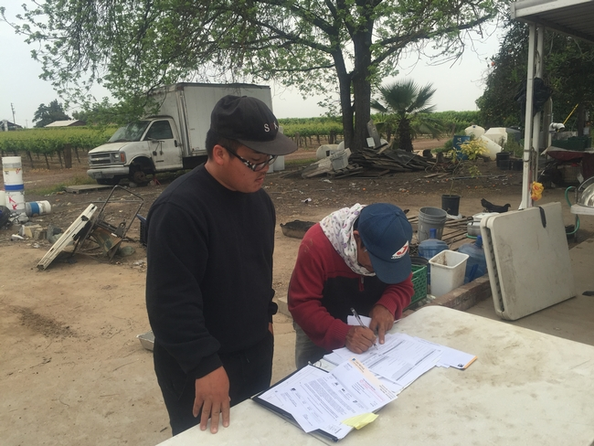 Xia Yang works with a Hmong farmer on making changes to energy billing.