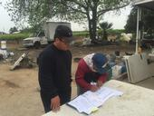 Xia Chang works with a Hmong farmer on making changes to energy billing.