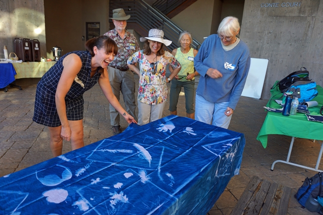 Artist Jessica Layton, left, shows a cyanotype mural project made by the group. The fabric was commercially treated with the cyanotype solutions and captured the silhouettes of a wide variety of objects, including hands, sunglasses and a water bottle.
