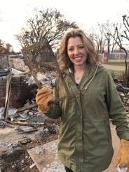 A homeowner holds a foundation vent found in the rubble of her home. Her house, built before the 2008 construction standards, had ¼-inch mesh screen that may have allowed embers to enter her home.