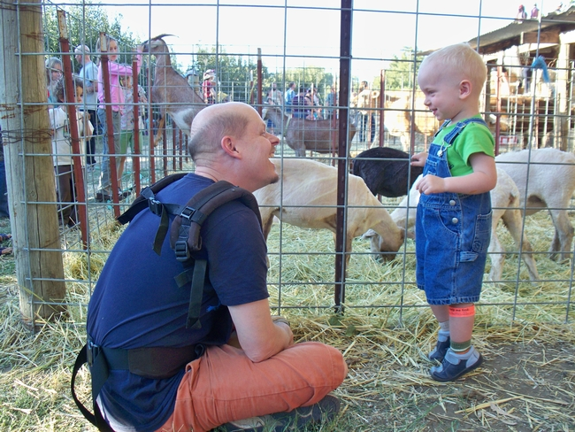 Father and son enjoy a petting zoo on a farm offering agritourism experiences.