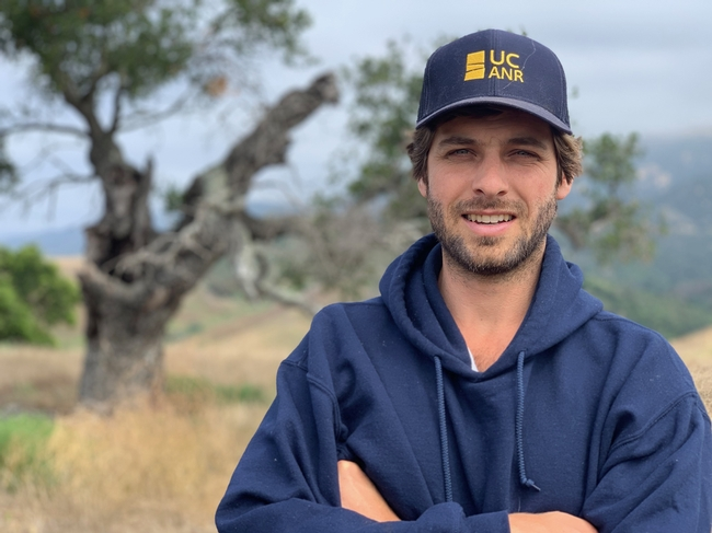 Matthew Shapero, wearing a navy blue hoodie and ANR logo hat, stands with arms folded across his chest while standing in a pastural setting.