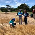 Maggie Reiter, in blue hat, examines naturalized area of a golf course Photo by James Hempfling