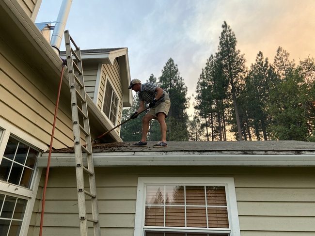 Ryan Tompkins stands on his roof raking moss, vegetative debris, and leaf litter from the gutters.
