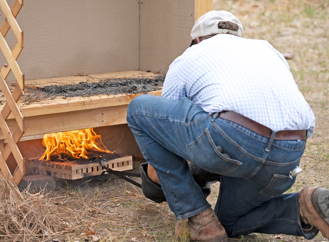 Ryan Tompkins, shown from behind, slides a flaming wooden block under a wood deck.