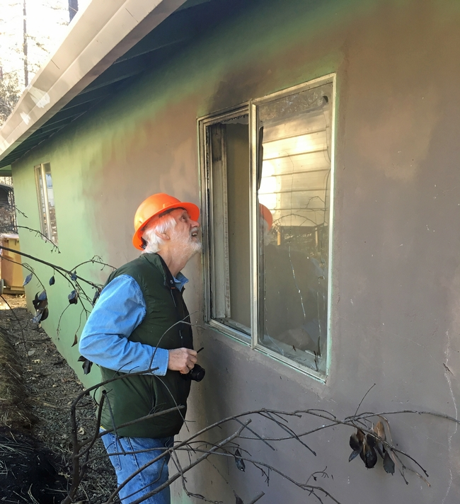Steve Quarles, UC Cooperative Extension advisor emeritus, looks at a garage attached to an older house in Paradise where the radiant heat from a nearby fence and line of planted vegetation ignited and were sufficiently hot enough to break the single pane glass. Photo by Yana Valachovic