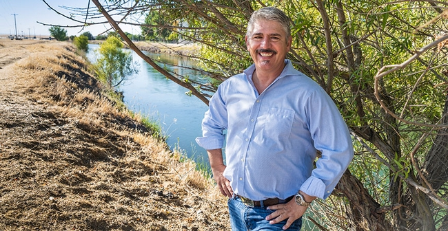 Josh Viers stands beside a small tree on a bank beside an irrigation canal in a rural setting.