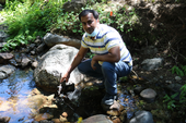Safeez Khan crouches on stones as he samples water in a mountain stream.