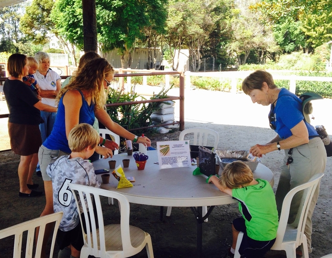 Master Gardener, Carole Rowland helps youth plant seeds to take home.