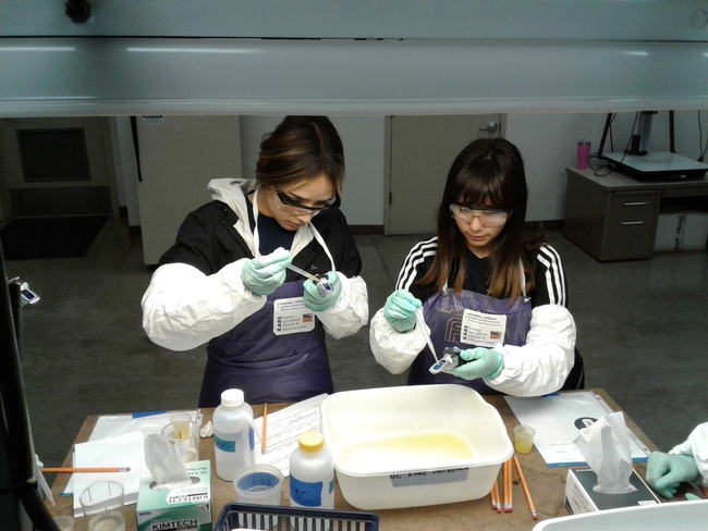 Two FARMS students check the sugar content of oranges.