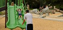 Maliah Garcia, 2, laughs as she slides with her father, Ken, at Westwood Park in Denver. (Hyoung Chang/The Denver Post via Getty Images) for Latino News Briefs Blog