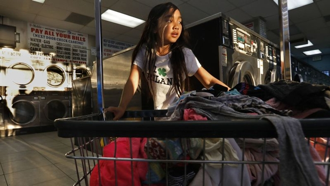 Isabella Kap, 8, helps her grandmother at the laundromat in Long Beach, where members of the large Cambodian community often lend money to one another through informal groups rather than use banks. (Carolyn Cole / Los Angeles Times)