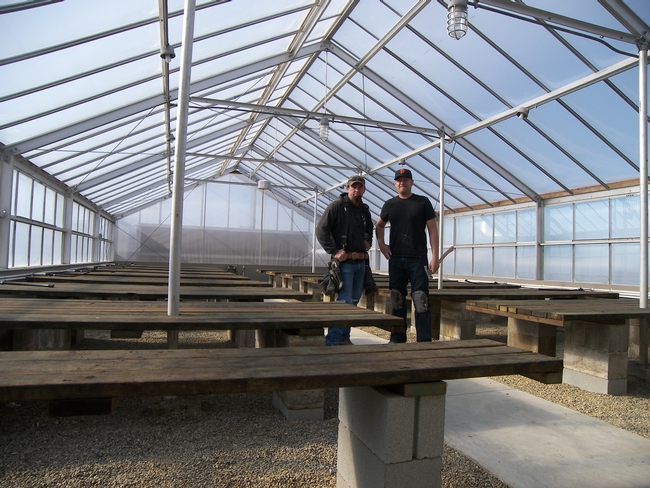 Physical Plant Mechanic Dan Seymore and assistant Dave Christiansen proudly show off the new greenhouse