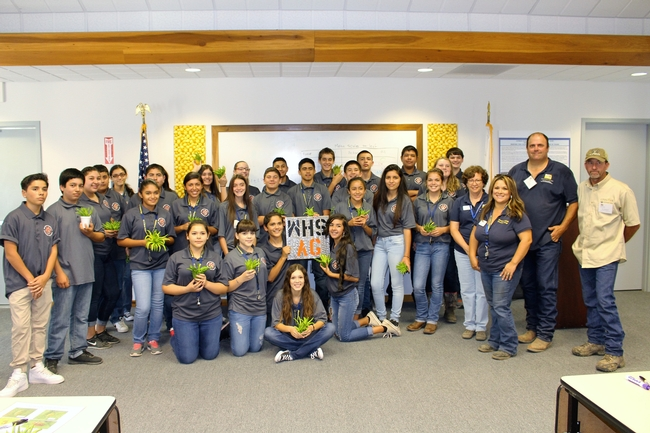 Woodlake Ag Academy students show off a plaque created in the ag mechanics workshop and take home some Buddha's Hand citrus fruit.