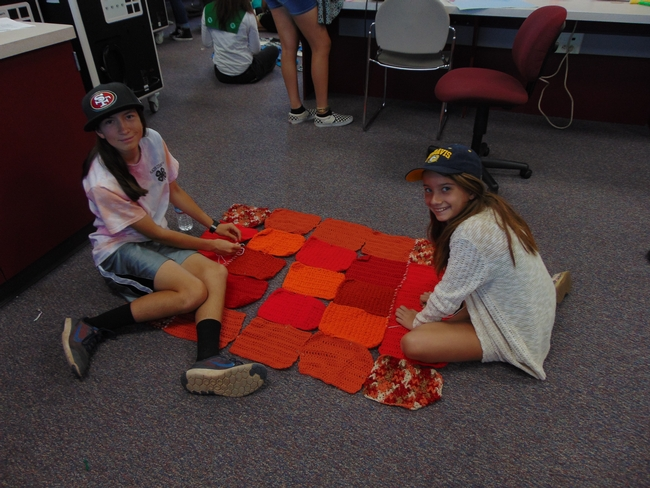 Two 4-H girls work together to piece their chosen knitted squares together using a whip stitch.