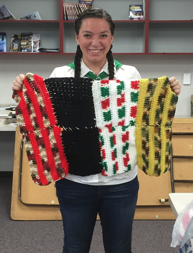Lydia holding a blanket assembled by 4-H Youth