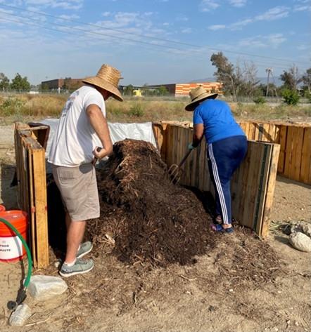 Master Gardeners Bart K. and Elizabeth C. turning compost