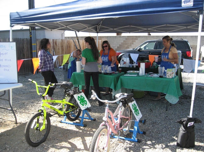 4-H Teens talk about nutrition with kids and demonstrate how to ride the Smoothy Bikes.