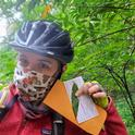 SOD Program Coordinator Kerry Wininger collects California Bay Laurel leaves for the Sudden Oak Death Blitz by bicycle while social distancing and wearing a mask made by SOD Specialist Master Gardener Janet Calhoon