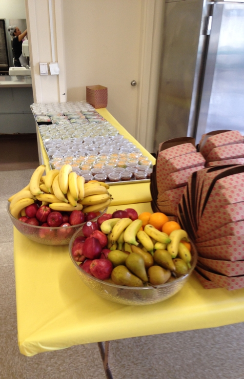 After: Fresh fruit in bowls is eye catching, and a yellow tablecloth brightens the serving line, giving it a cafe feel.