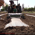 Laying plastic with a tractor for soil solarization