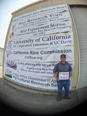 Aaron Alvarez, UC Davis graduate student, accepts D. Marlin Brandon Rice Research Fellowship award during the California Rice Field Day 2021.