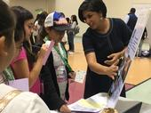 During the career fair, an Engineer speaks with youth about what she does for her job