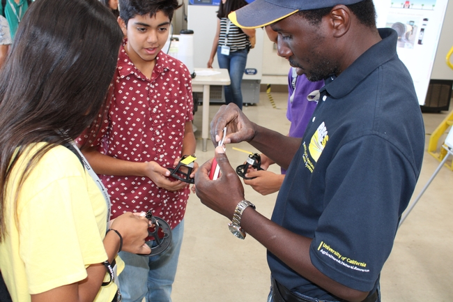 Dr. Peter Larbi interacting with student volunteers to demonstrate spray coverage during workshop.