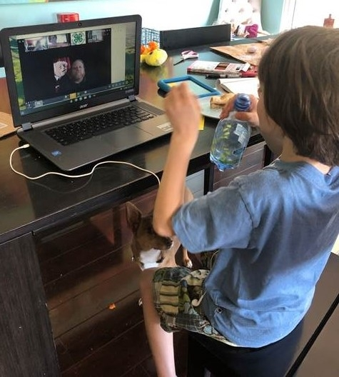 Youth drinks a bottle of water while sitting in front of a laptop. On the laptop is the Zoom application showing the video of a 4-H Advisor.